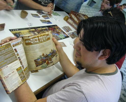 Juano revisando las reglas del juego de mesa Dice Town