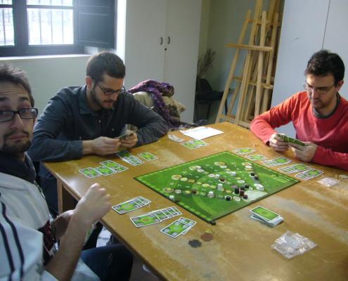 Tres jugadores disputando una partida al juego de mesa Keltis