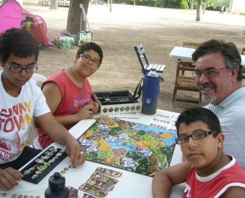 Varios visitantes jugando al juego de mesa Small World